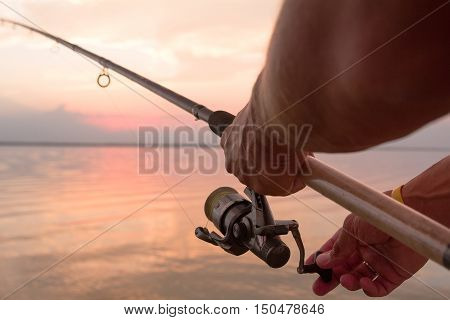 Fisher's hands holding reel, fishing at the sunset at lake