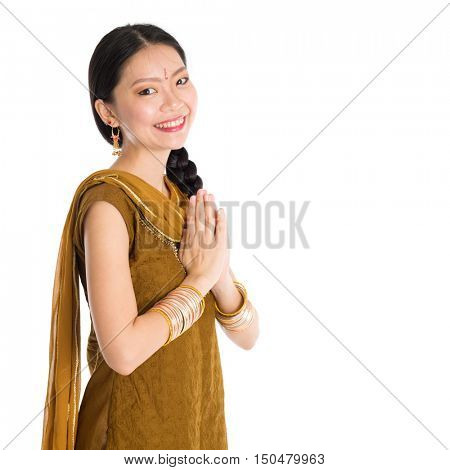 Young mixed race Indian Chinese girl in traditional punjabi dress greeting gesture, standing isolated on white background.