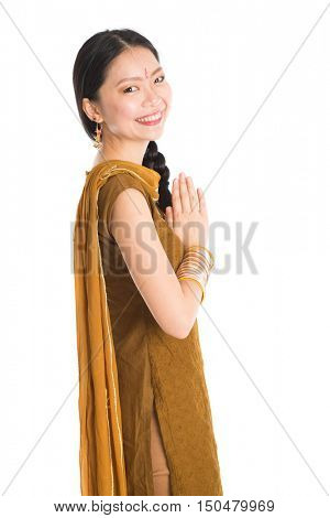 Portrait of young mixed race Indian Chinese female in traditional punjabi dress greeting, standing isolated on white background.