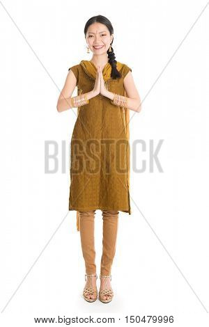 Portrait of young mixed race Indian Chinese girl in traditional punjabi dress greeting, full length standing isolated on white background.
