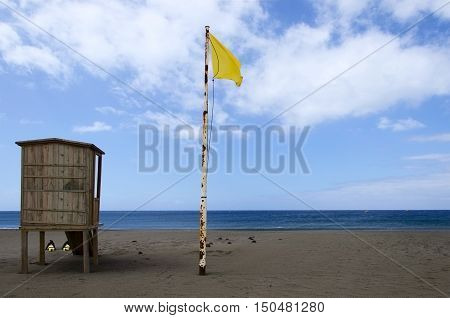 Lifeguard tower with yellow flag waving over the blue skyon the beach