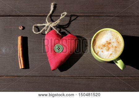 flat layout with cinnamon stick frothy cappuccino and a heart of soft tissue / mystery about coffee