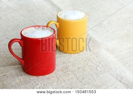 frothy cappuccino in red and yellow circle on the surface of the tissue / warm colors coffee warming