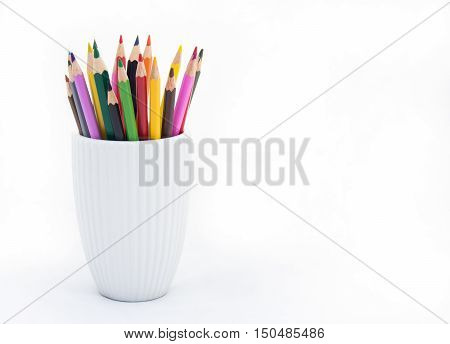 Colored pencils in a white porcelain cup. Copy space