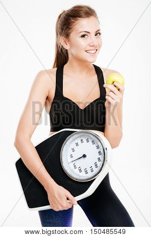 Happy young sportswoman holding weight scales and holding green apple isolated on a white background