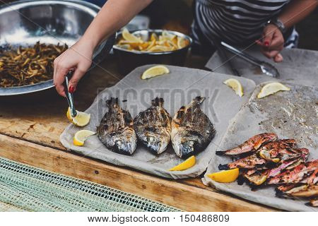 Plenty of dorado and red mullet fish grilled at barbecue. Seafood bbq outdoors at picnic, party. Street food vendor makes take away on big tray. Grill crispy roasted fish with lemon