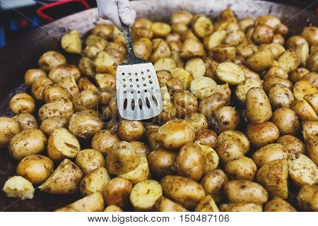 Country fair cooking. Roasted potatoes cooked by vendor outdoors in big metal cauldron pot. Cookout meals with bbq spatula. Fresh organic, healthy snack, potatoes on grill. Street food, fast food.