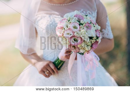 The bride holds a bouquet charming in her wedding day