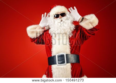 Modern Santa Claus in sunglasses over Christmas red background.