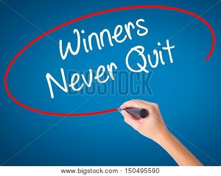 Man Hand Writing Winners Never Quit With Black Marker On Visual Screen