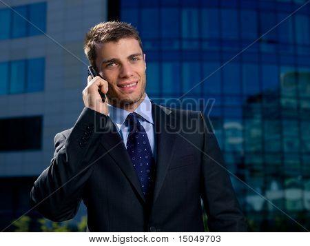 Retrato de homem de negócios fora do edifício, usando telefone celular