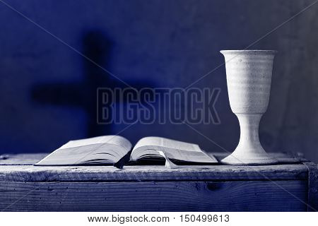 open bible with chalice of wine in the churchselective focus