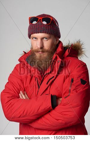 Portrait of a serious man wearing red winter jacket with mustache and beard with intense look