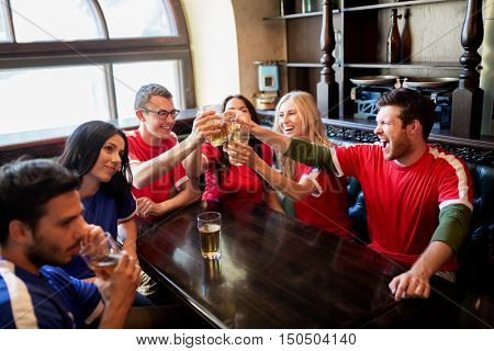 sport, soccer, people and leisure concept - happy friends or football fans clinking beer glasses at bar or pub, supporting two teams with different shirt color