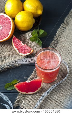 Glass of freshly squeezed grapefruit juice and measuring tape on burlap napkin on wooden table. Drink for dieting.