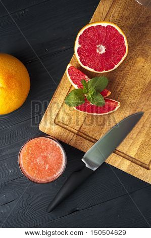 Freshly squeezed grapefruit juice with mint, grapefruit slices and knife on wooden table. Drink for dieting.