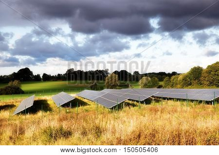 Solar panels on a field in a rural autumn landscape in the warm sunlight under a cloudy sky soft focus