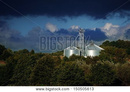 Industrial silo from metal shines in the light in a rural landscape with dark trees under a stormy sky in autumn copy space