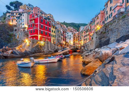 Riomaggiore fishing village during evening twilight blue hour, seascape in Five lands, Cinque Terre National Park, Liguria, Italy.