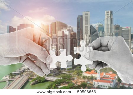 Hands putting partnership puzzle pieces together on skyscraper building in background. Partnership network concept