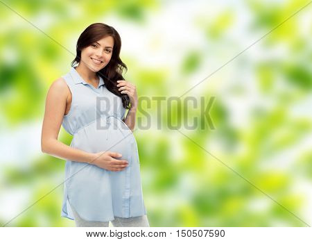 pregnancy, motherhood, people and expectation concept - happy pregnant woman touching her big belly over green natural background