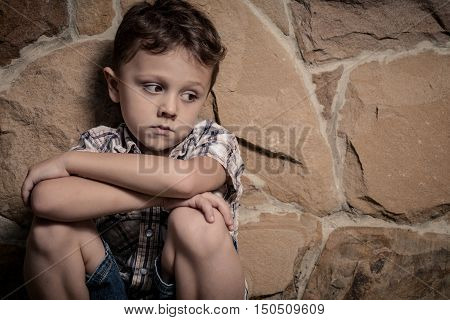 sad little boy sitting near a wall