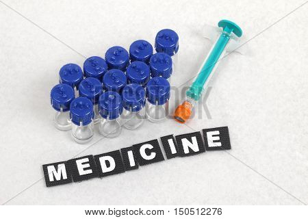 Bunch of vials with medicine and syringe on blotch paper