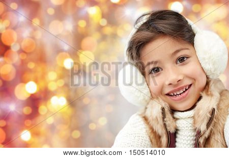 winter, people, christmas and clothing concept - happy little girl wearing earmuffs and gloves over golden holidays lights background