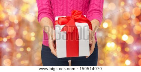 christmas, holidays and people concept - close up of woman in pink sweater holding gift box over lights background