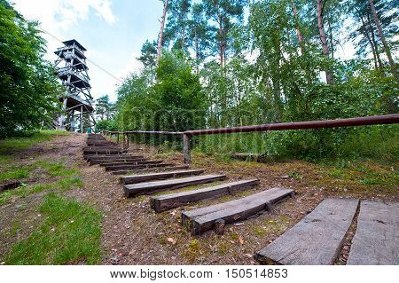 Steps and railing leading to wooden watchtower in forest on sunny day.