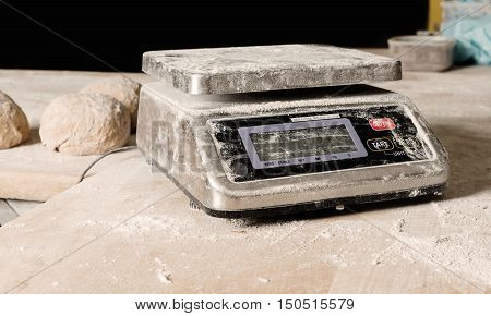 Digital weight table sprinkled with flour on the wooden table