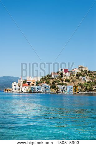 View over bay of Kastelorizo. Island coast with typical colorful Greek houses and clear turquoise sea water. Dodecanese, Greece