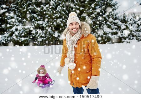childhood, sledding, leisure, season and people concept - happy man or father carrying little kid on sled in winter