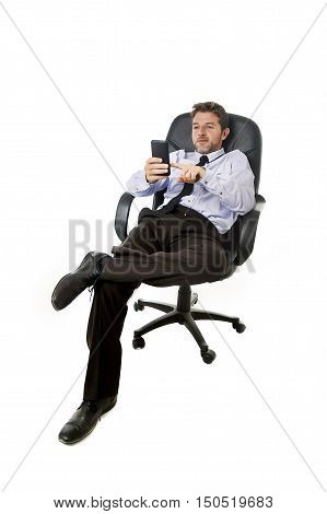 young happy attractive businessman leaning relaxed sitting on office chair networking on mobile phone in success and relax at work concept and successful satisfied business man