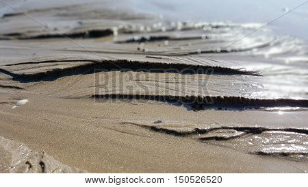 Wet dunes of sand in afternoon sun. Macro shoot with close focus.