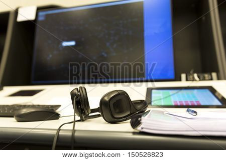 Sofia Bulgaria - September 12 2016: Bullgaria's Air Traffic Services Authority control center room. Controller's headsets on the desk in front of the control computer monitor. No people.