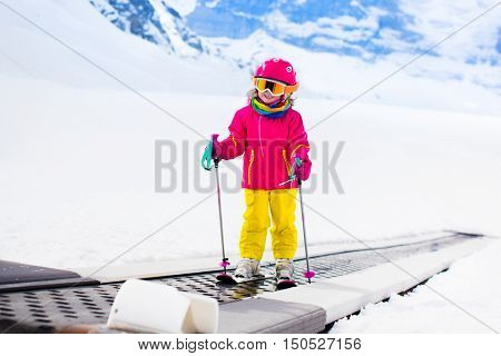 Child on magic carpet ski lift going uphill in the mountains on snowy winter day. Kids in winter sport school in alpine resort. Family fun in the snow. Little skier learning and exercising on a slope.