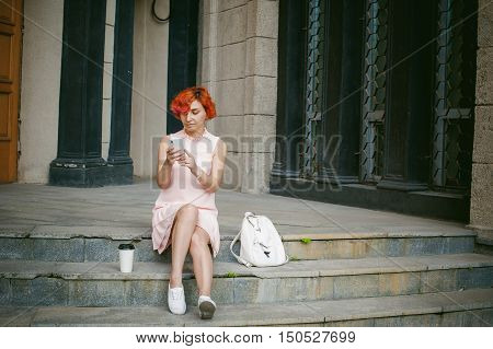 Girl Doing Selfie. Woman With Dyed Red Hair In A Pale Pink Dress With A Backpack White Color Drinkin