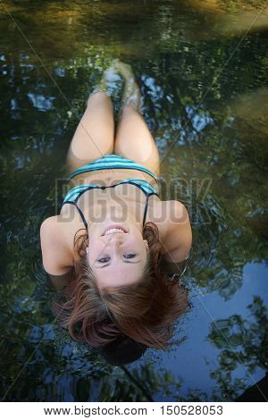 upside down portrait of bikini girl lying in shallow water at bathing lake