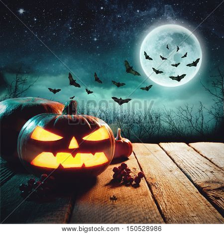 Halloween Pumpkins On Wood In A Spooky Forest At Night. Studio shot. Elements of this image furnished by NASA