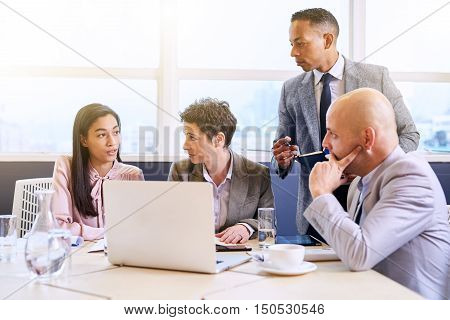 Mature male businessman supervising his subordinates as they work in a modern conference room with a large window behind them allowing bright natural light to flood the room.