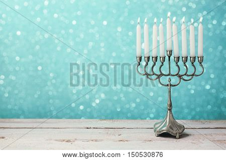 Menorah with candles for Hanukkah celebration over bokeh background