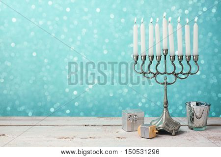 Jewish holiday Hanukkah celebration with menorah dreidel and gifts on wooden table