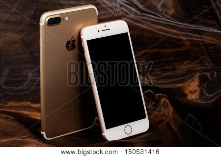 Koszalin, Poland- October  06 , 2016: Golden iPhone 7 Plus and pink iPhone 7. Devices displaying the applications on the home screen. The iPhone 7 Plus and iPhone 7 is smart phone with multi touch screen produced by Apple Computer, Inc.