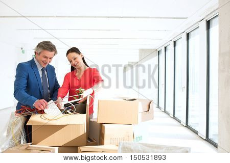 Business people unpacking cardboard boxes in new office