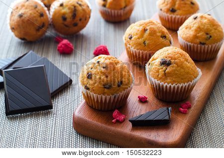 Little chocolate muffins in paper cupcake holder with crushed chocolate and dried raspberries on the wooden tray