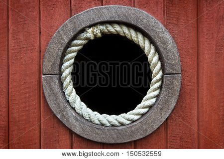 Close-up of a boat porthole rounded with rope against a wood background.