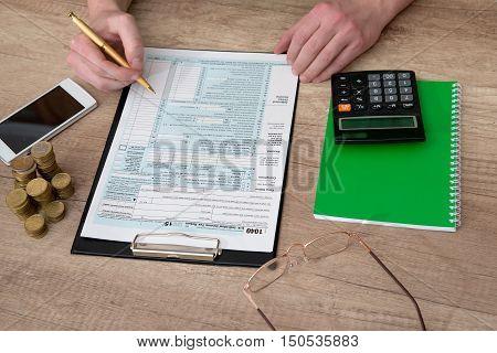 stressed man filling a 1040 tax form