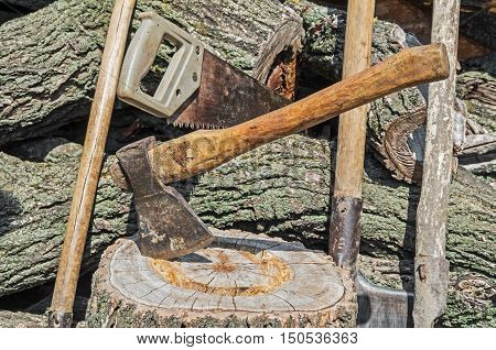 Set of old rural tools on a background of a heap of logs