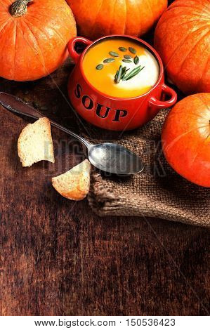 Pumpkin soup with fresh pumpkins and bread crouton on wooden table. Bowl of pumpkin soup with copy space close up